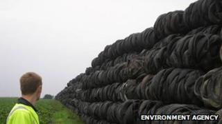 Man looks at stockpile of tyres in a field
