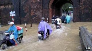 This picture taken November 8, 2011 by the Vietnam News Agency shows motorcyclists riding through a flooded gate of the old citadel in the central city of Hue