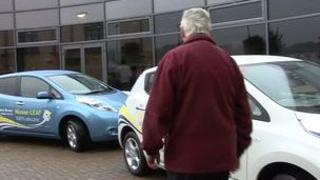 Man next to two Nissan leaf electric cars