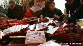 People examine pirated DVD disks in Beijing (file photo)