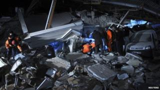 Rescue workers search for survivors at a collapsed building in Van, eastern Turkey