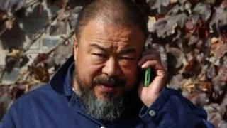 Ai Weiwei talks on his phone outside his studio on 8 November 2011