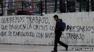 Man in Madrid walks past wall daubed with graffiti demanding jobs