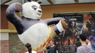 People pose for photos by movie advertising outside a cinema in Beijing