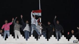 Pro-Syrian government supporters raise the Syrian flag on the roof of the Qatar embassy in Damascus on 12 November 2011