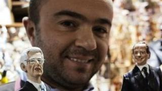 Man holding Berlusconi and Monti figurines