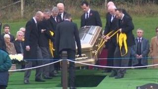 Sir Jimmy Savile's coffin being lowered into the ground