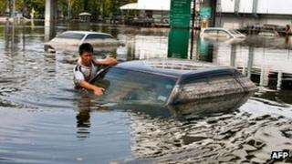 A man takes advantage of receded flood waters to check his car in the parking lot next to the Don Muang Airport on November 11, 2011.