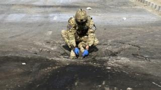 A foreign soldier investigates the crater caused by an explosion at the site of a suicide attack in Kabul October 29, 2011.