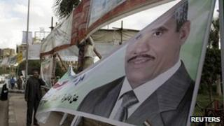 An election worker hangs a candidate's poster in Cairo - 14 November 2011