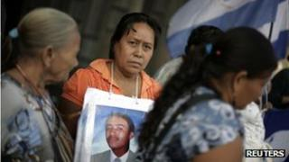 Women with pictures of missing family members stand outside the Basilica of the Virgen of Guadalupe