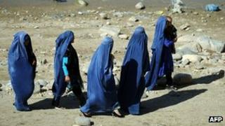 A group of burqa-clad Afghan women walk along the shore at The Band-e-Qargha Gulestan Park in Kabul on October 14, 2011