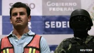 """Juan Gabriel Orozco Favela (L), alias """"Gasca"""", is presented by a Mexican soldier to the media in Mexico City November 15, 2011."""