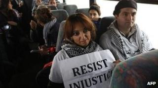 Two Palestinian activists sit inside as Israeli bus as it rides between a bus stop outside the West Bank Jewish settlement of Migron, near Ramallah, and a checkpoint leading to Jerusalem
