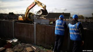 digger and two men stood by fence