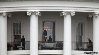 Law enforcement officials examine a White House window for damage