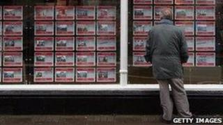 Man looking at houses for sale in shop window