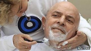 Former Brazilian President Lula da Silva poses with his wife after having his hair and beard shaved off