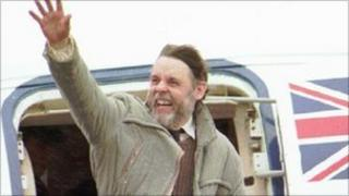 Terry Waite waves from a plane after landing in England