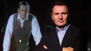 Liam Neeson stands in front of a holographic image during the launch of The War of The Worlds 2012 National Musical Tour