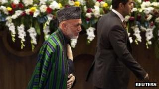 Afghan President Hamid Karzai gestures after his speech at a Loya Jirga, or grand assembly, in Kabul, 19 November 2011