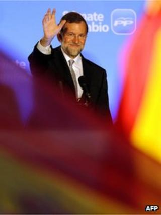 Leader of the Spanish Popular Party (PP) Mariano Rajoy (C) waves to supporters from the balcony of the PP headquarters in Madrid on 20 November 2011