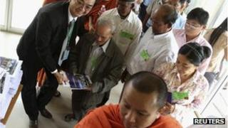 Survivors of Khmer Rouge brutality are guided into the court, November 21, 2011