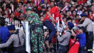 Indonesian security officials evacuate supporters of the Indonesia football team in Jakarta.