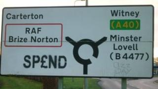 SP£ND tag on a road sign
