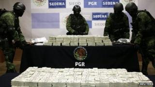 Mexican soldiers arrange stacks of money seized in Tijuana