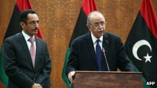 Abdel Hafiz Ghoga (left), of the National Transitional Council listens to Libya's interim PM Abdurrahim al-Keib announce his new cabinet line-up on 22 November 2011