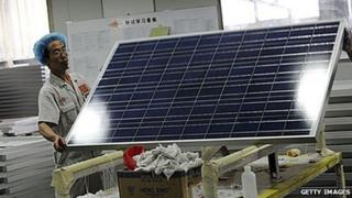 A worker lifts a solar panel in the Yingli Solar factory in Baoding, Hebei province