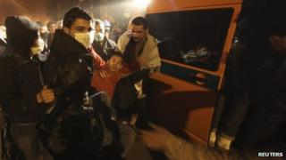 Protesters assist an injured fellow protester into an ambulance after clashes with the army and riot police
