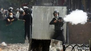 A riot policeman fires a shotgun at protesters during clashes in Tahir Square