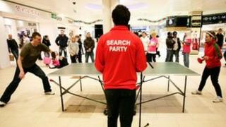 A game of ping pong being played in a shopping centre