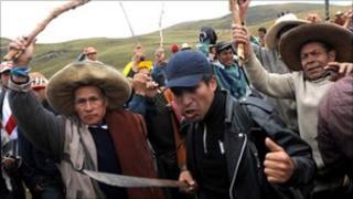 Peruvian protesters brandishing sticks and machetes