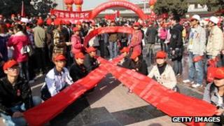 AIDS activists form a red ribbon, marking the World's AIDS day in Zhengzhou, central China's Henan province, 1 December 2010