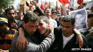 Family members mourn during a funeral for a protester on 18 February 2011 in Sitra, Bahrain