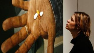 A lady views Damien Hirst's oil on canvas painting 'HIV AIDS, Drugs Combination'