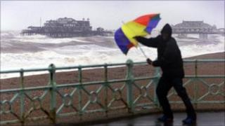 Man with brolly in strong winds on Brighton seafront
