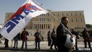 Trade unionists gather near the Greek parliament in Athens, 1 December