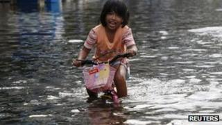 A girl rides through a flooded street in Nonthaburi province