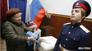A woman carrying a child casts her ballot next to a Russian cossak (R) at a polling station in Rostov-on-Don