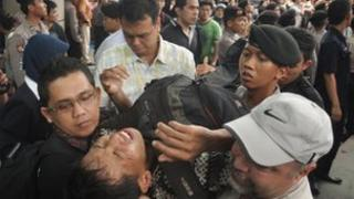 Security personnel evacuate a Indonesian man after he collapsed while queueing for discounted BlackBerry smart phones at a mall in Jakarta