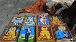 A woman on the pavement selling posters of Ambedkar and the Buddha