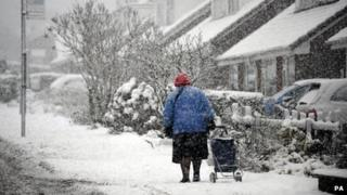 A woman drags a trolley through snow