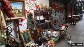 A shop owner sits on an old armchair at his open air antique shop in central Athens October 2011.