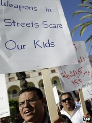 Libyans hold signs during a rally to demand the collection of weapons in Tripoli (20 November 2011)