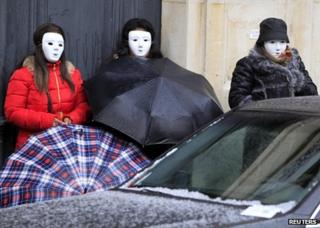 Prostitutes wearing masks rally outside the National Assembly in Paris, 6 December