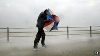 A man holding an umbrella in windy weather